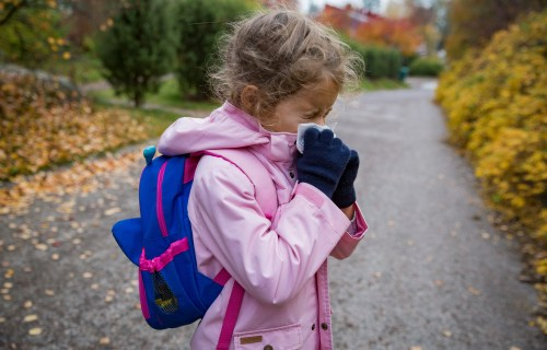 Sick little girl blowing nose while on her way to school