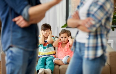 Siblings covering ears while parents fight