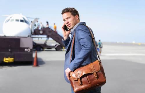 Man talking on phone before boarding airplane