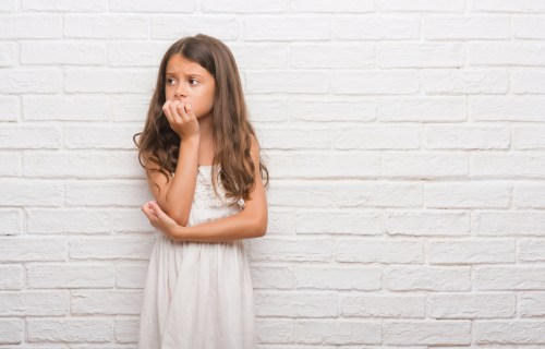 Young anxious girl biting her nails