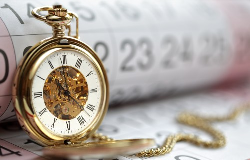 Time: Gold pocket watch on top of calendar