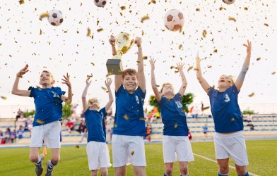 Youth soccer team celebrating with trophy