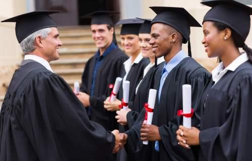 Students at graduation, dean gives diplomas to graduates