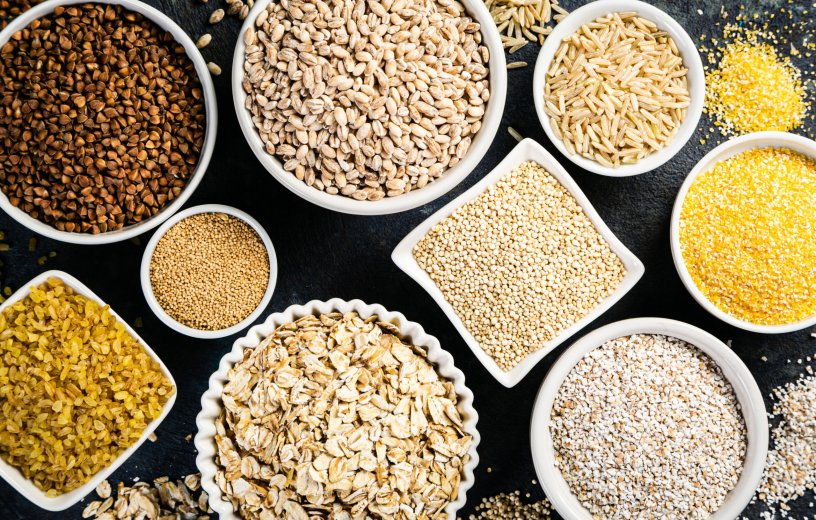 Selection of whole grains in white bowls - rice, oats, buckwheat, bulgur, porridge, barley, quinoa, amaranth