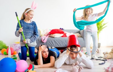 Stressed out, tired parents on floor with wild young children in messy home
