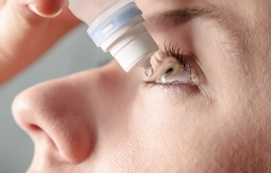 Woman putting eye drops in eyes