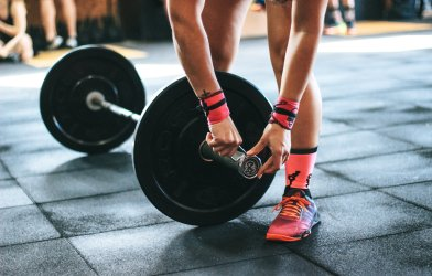 Person weight lifting at gym using barbell