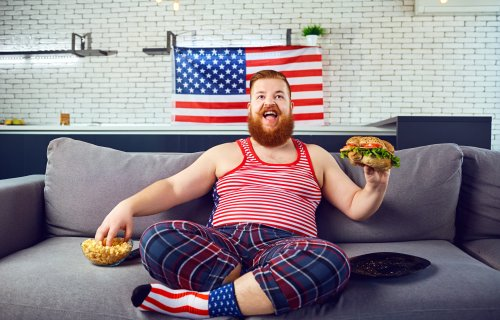 Overweight funny man eating a burger, snacking while sitting on the couch