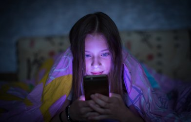 Teen girl in bed looking at smartphone at night