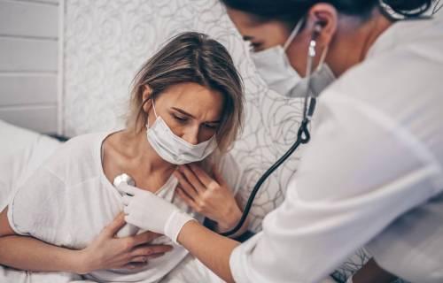 Doctor listening to coronavirus / COVID-19 patient having trouble breathing