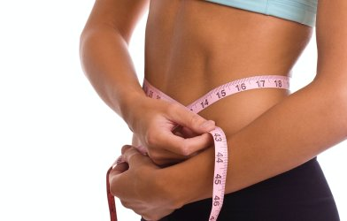 Weight loss: woman measuring her waist size