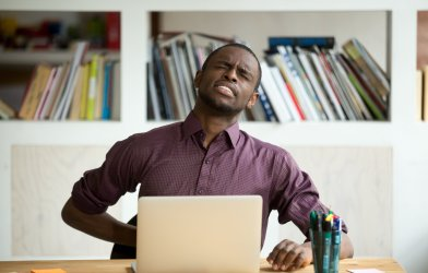 Man bothered by back pain while working at desk, home office