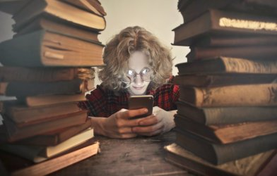 Teen looking at smartphone surrounded by books
