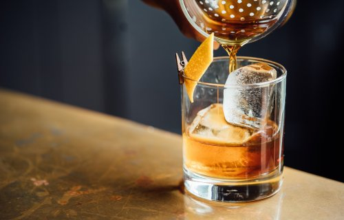 Bartender pouring an old fashioned, glass of whiskey alcohol