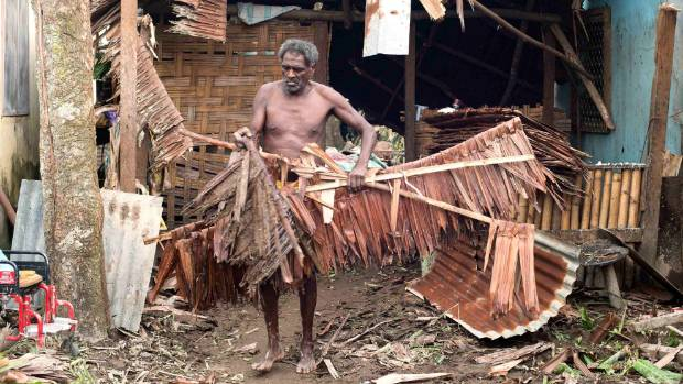 A local resident moves debris from near his damaged home after Cyclone Pam hit Port Vila, the capital city of the Pacific island nation of Vanuatu.