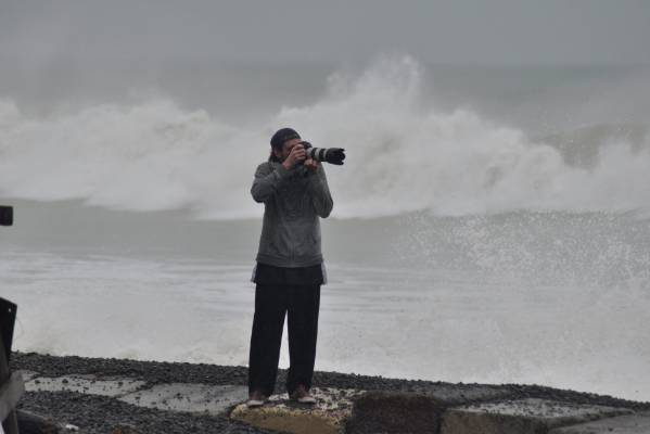 Freelance photographer Andrew Brunton snaps away as waves crash in the background along the Hawke's Bay coast at Haumoana