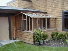 This energy efficient greenhouse is tucked next to the house. A lean-to greenhouse has fewer surfaces exposed