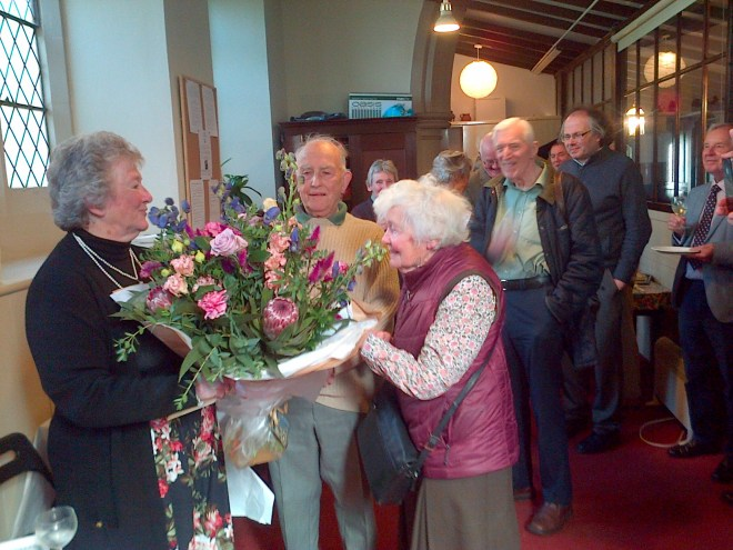 Anne Jarman is presented with flowers by Anne Clutterbuck during the party to thank her for all the wonderful years of organising parties for the congregation of St Vincent's. Anne's husband Alan looks on. 5th September 2015. Photo by Allan Maclean.