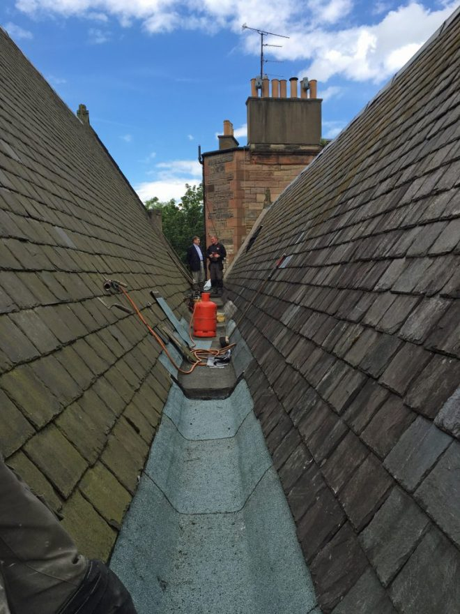 The Rector (left) talking to roofer Raymond Ewing during repair work in June 2016