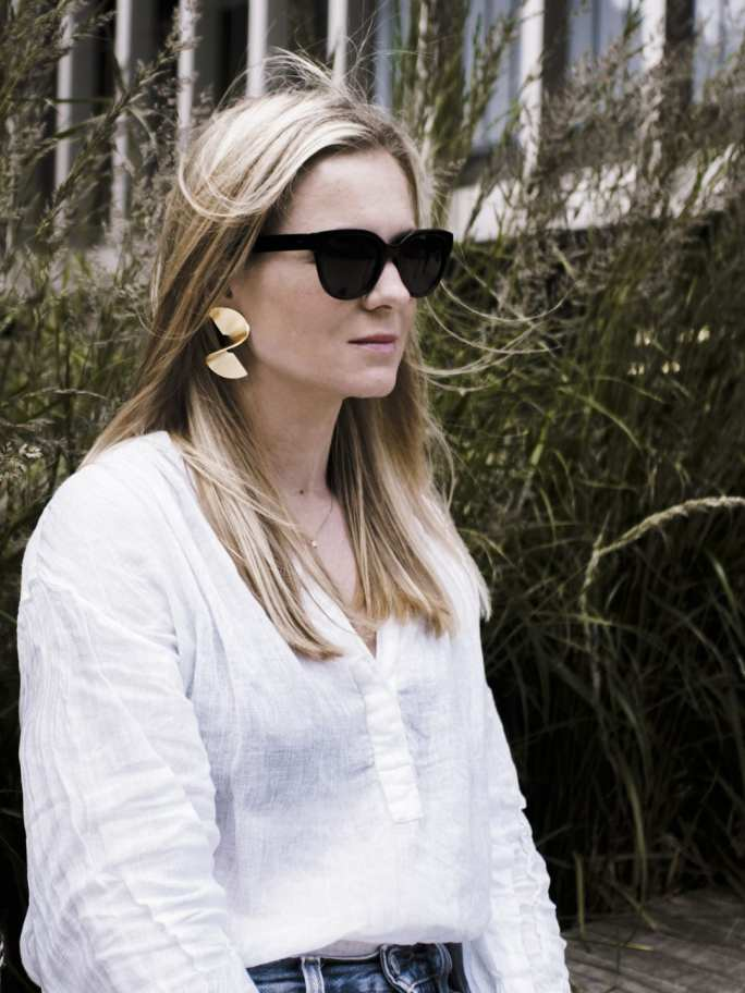 Vikki wears The White Company Linen Blouse, Finery statement earrings and Ace & Tate black sunglasses
