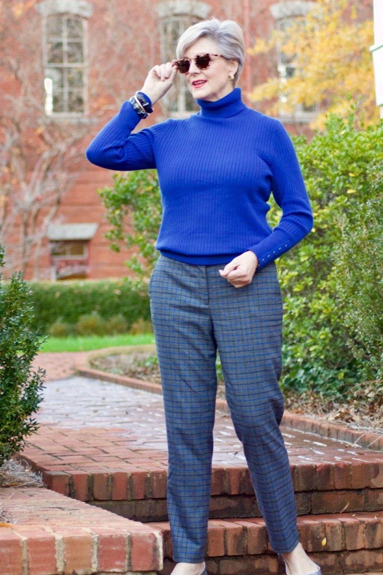 beth from style at a certain age wears plaid pants, cobalt blue turtleneck, green wool coat, blackwatch plaid cashmere scarf, and green beanie