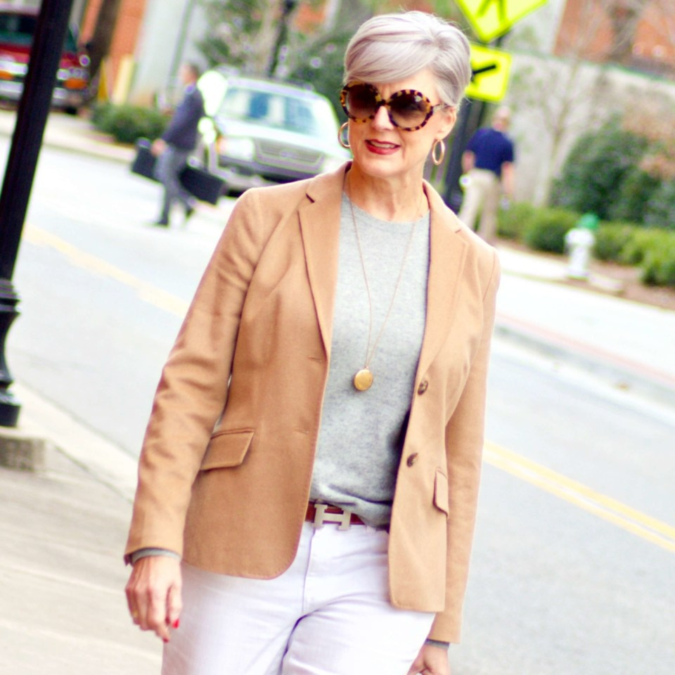 beth from Style at a Certain Age wears a camel blazer, grey cashmere crewneck, white denim, and leopard shoes