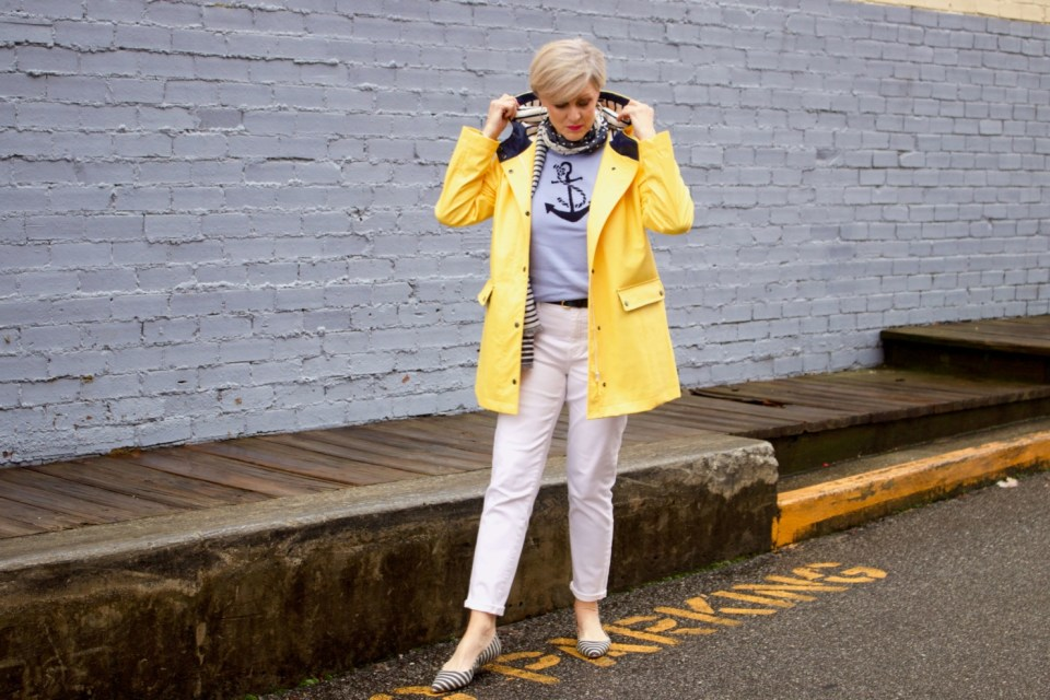 beth from Style at a Certain Age wears a yellow slicker from Talbots, white denim, anchor sweater, polka dot and striped scarf, and striped flats