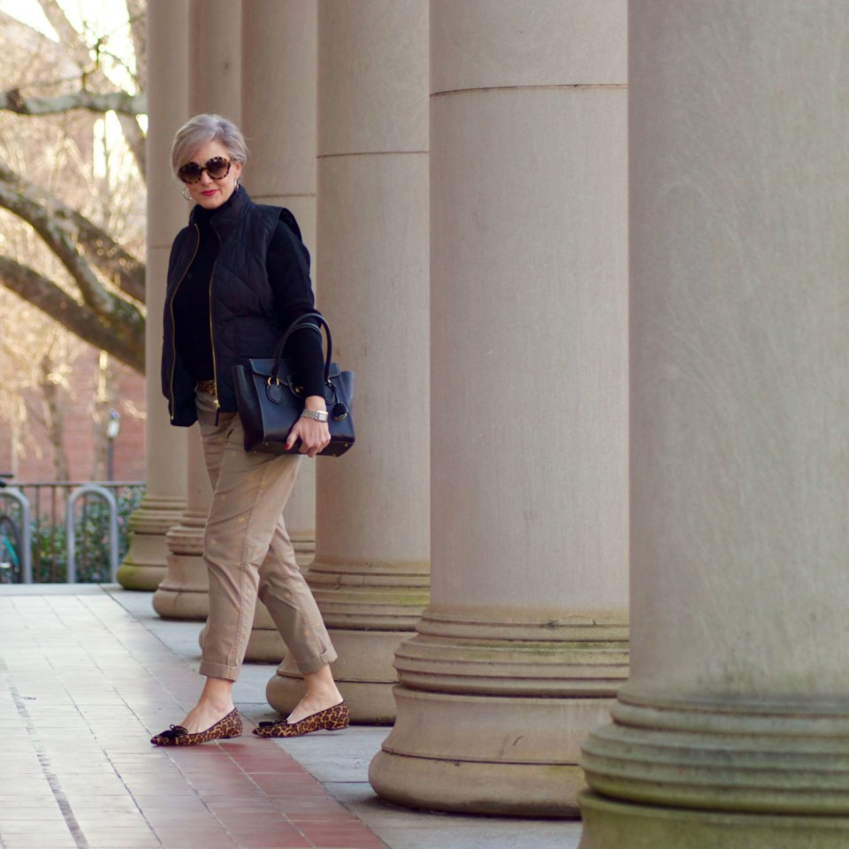 beth from Style at a Certain Age wears J.Crew polka dot chinos, Everlane cashmere waffle turtleneck, J.Crew Factory puffer vest, and Ann Taylor leopard flats