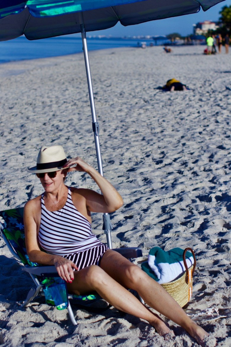 beth from Style at a Certain Age wears beach essentials, Ralph Lauren striped one-piece swimsuit, Tory Burch cover-up, jelly flip-flops, panama hat, and straw tote