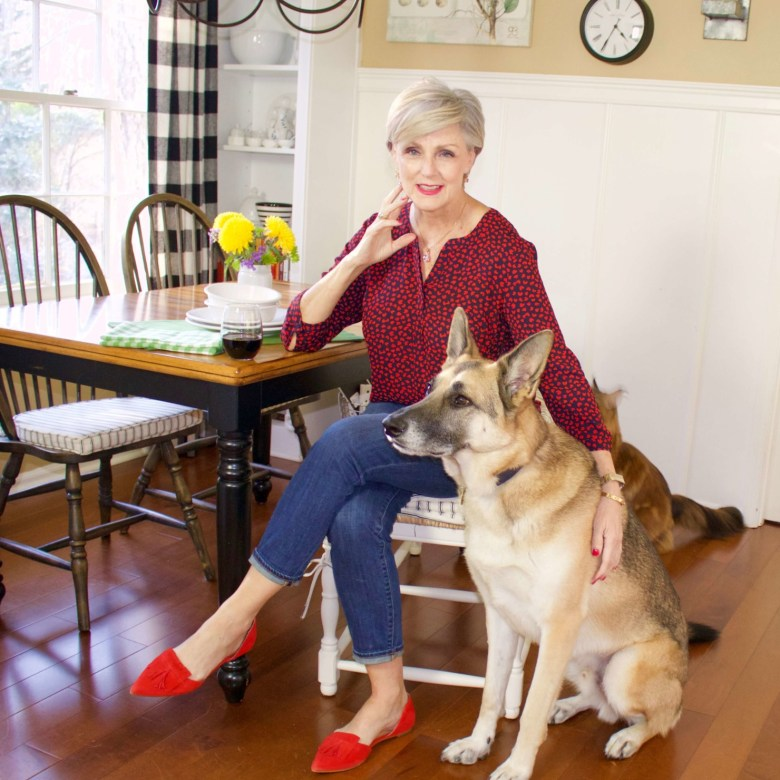 beth from Style at a Certain Age wears a Talbots red heart blouse, girlfriend jeans, and red shoes