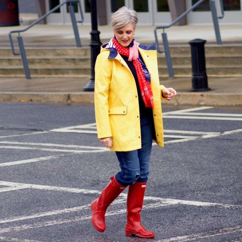 beth from Style at a Certain Age wears Hunter high gloss red rain boots, navy turtleneck, vintage straight jeans, yellow raincoat, and polka dot scarf
