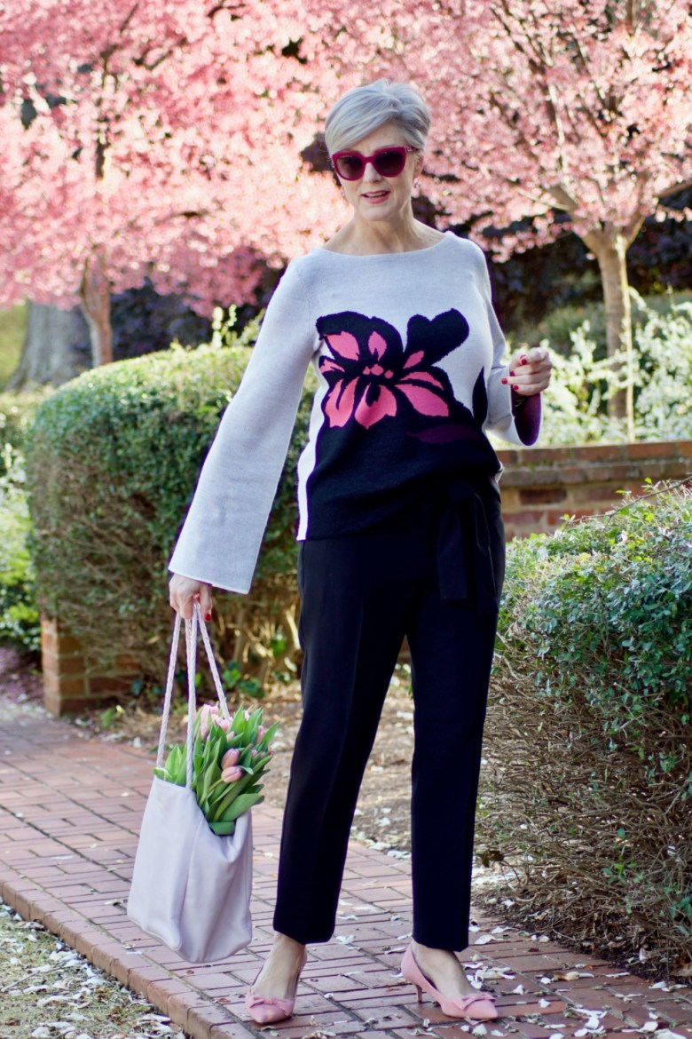 beth from Style at a Certain Age wears an Ann Taylor floral sweater, black ankle tie pants, and pink kitten heels
