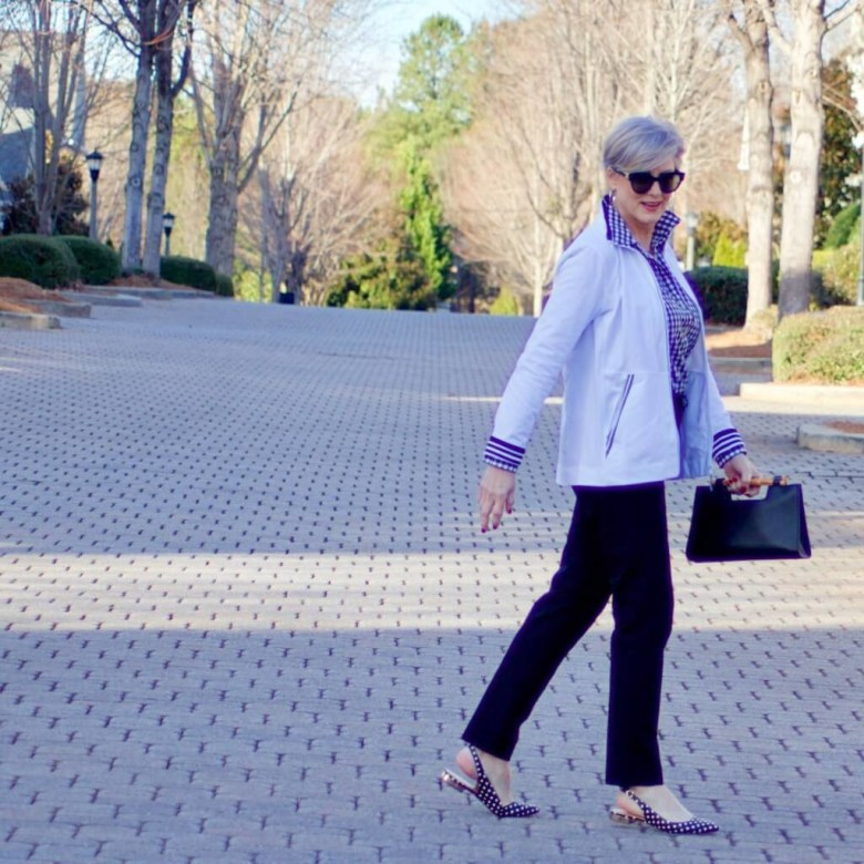 beth from Style at a Certain Age wears a gingham button up, black hampton pants, white track jacket, edison polka dot slingbacks