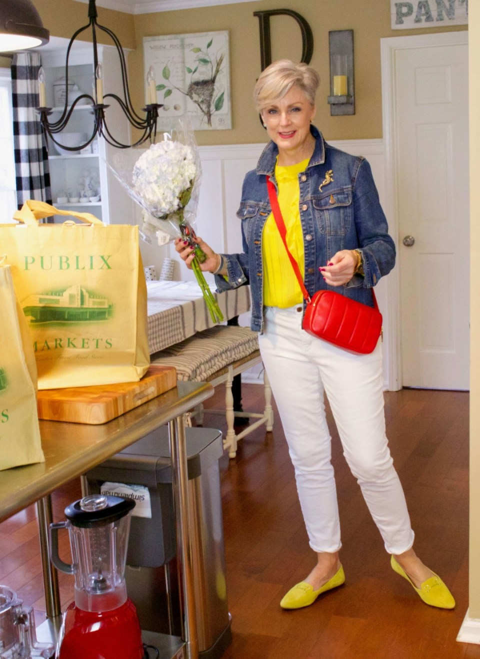 beth from Style at a Certain Age wears a ruffled yellow blouse, white denim, jean jacket, suede driving mocs, and a red camera handbag