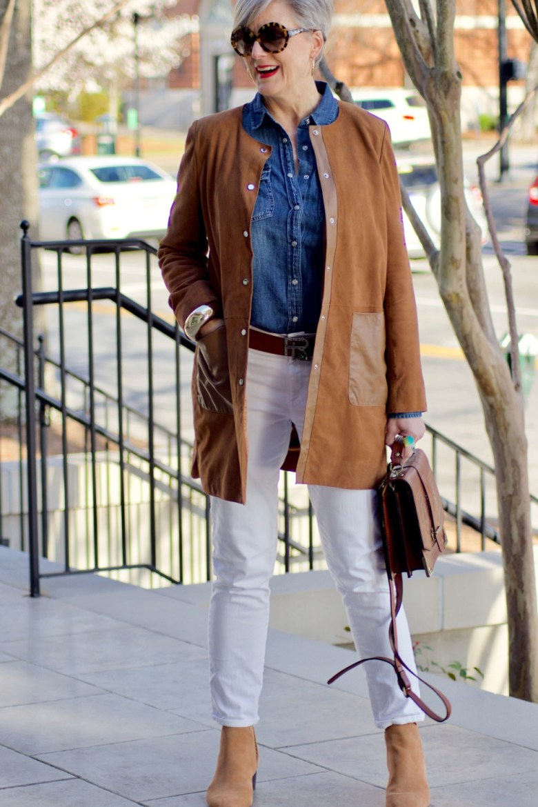 beth from Style at a Certain Age wears white denim, chambray shirt, suede jacket and booties