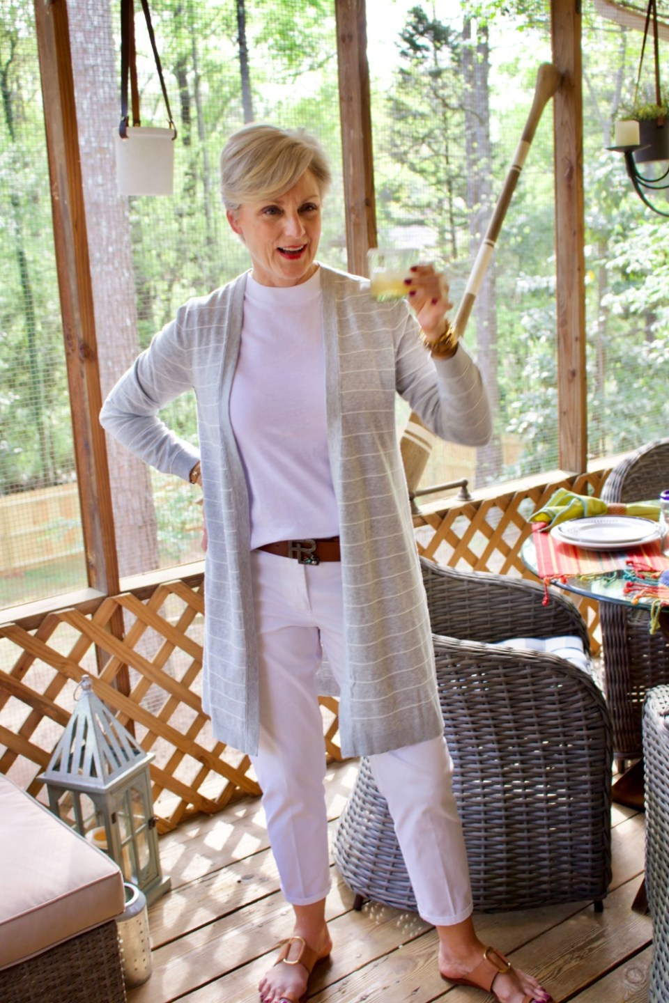 beth from Style at a Certain Age wears white girlfriend chinos, white muscle tee, gray cardigan, and brown sandals