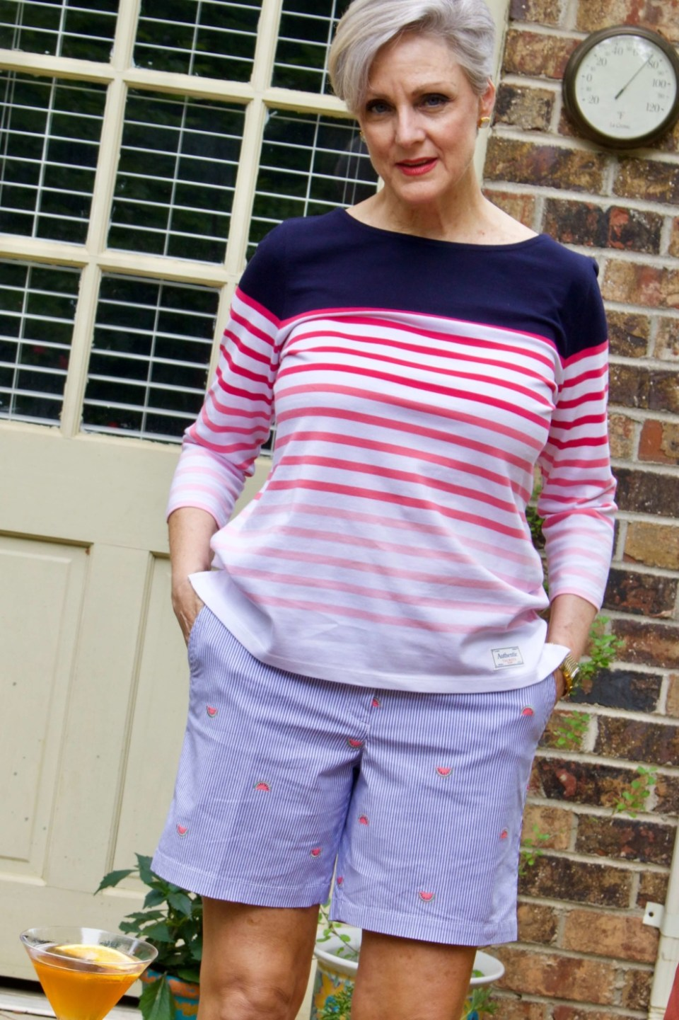 beth from Style at a Certain Age wears watermelon print shorts, striped tee, white jacket and jack rodgers sandals