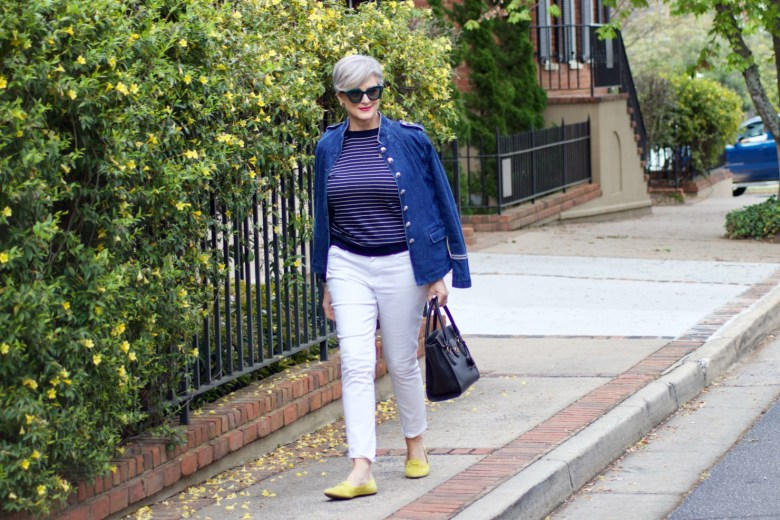 beth from Style at a Certain Age wears a denim military jacket, striped sweater, and white denim