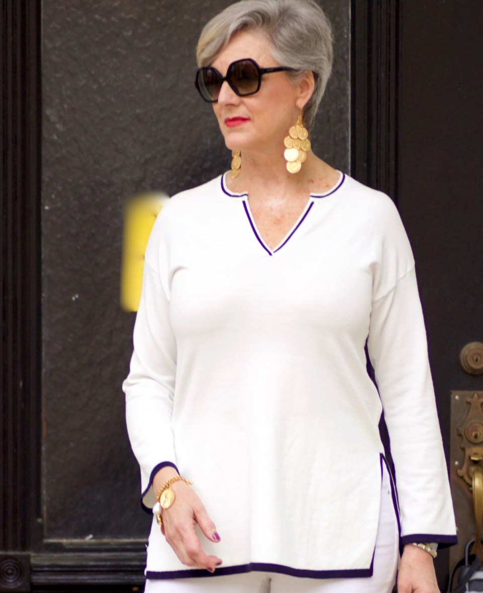 beth from Style at a Certain Age wears gold coin chandelier earrings, gold charm bracelet
