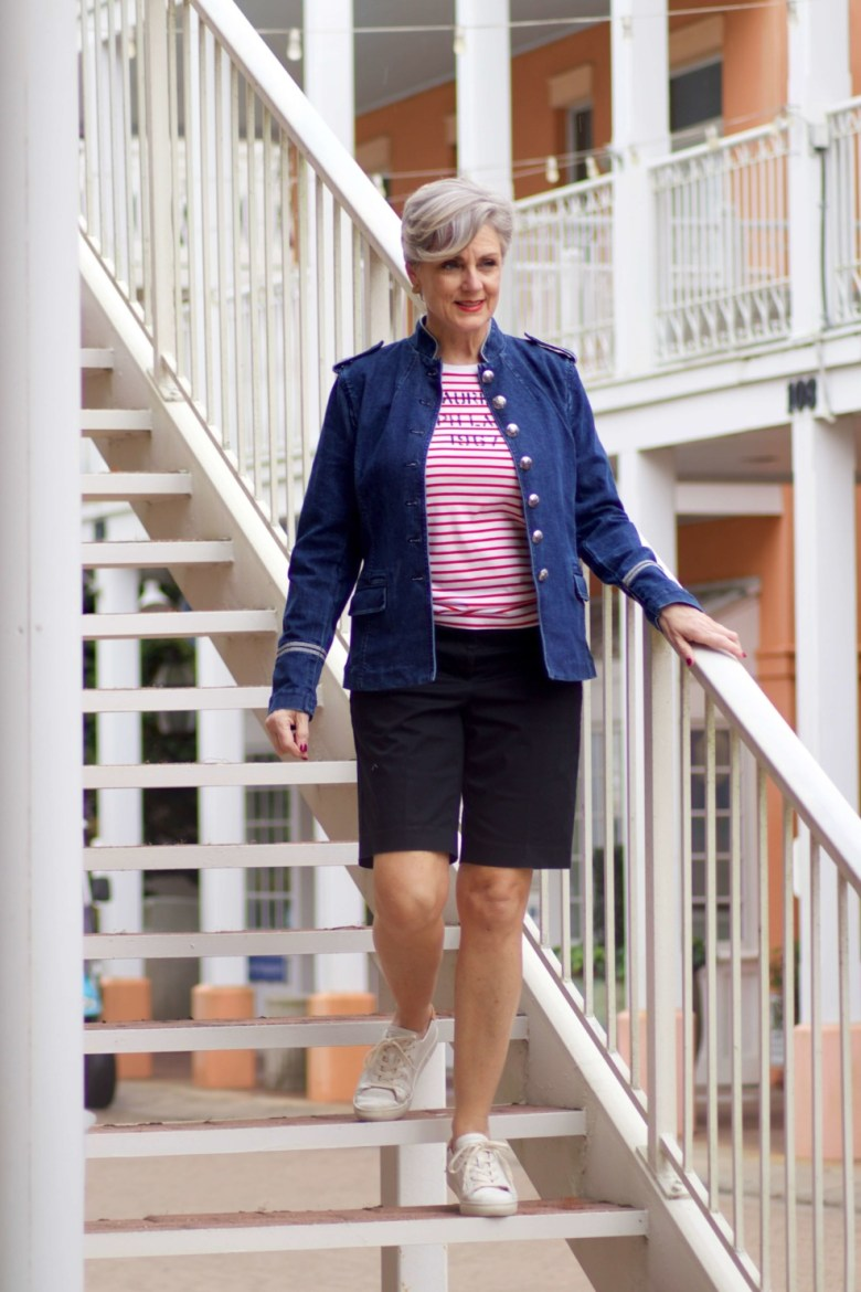 beth from Style at a Certain Age wears a military inspired denim jacket, red stripe tee, black bermuda shorts, and white tennis shoes