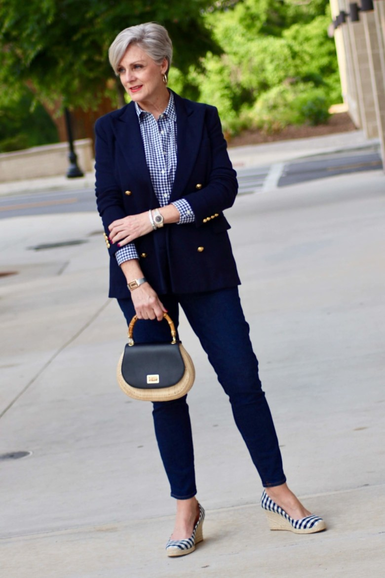 beth from Style at a Certain Age wears a lightweight blazer, gingham shirt, skinny jeans, espadrilles and wicker handbag