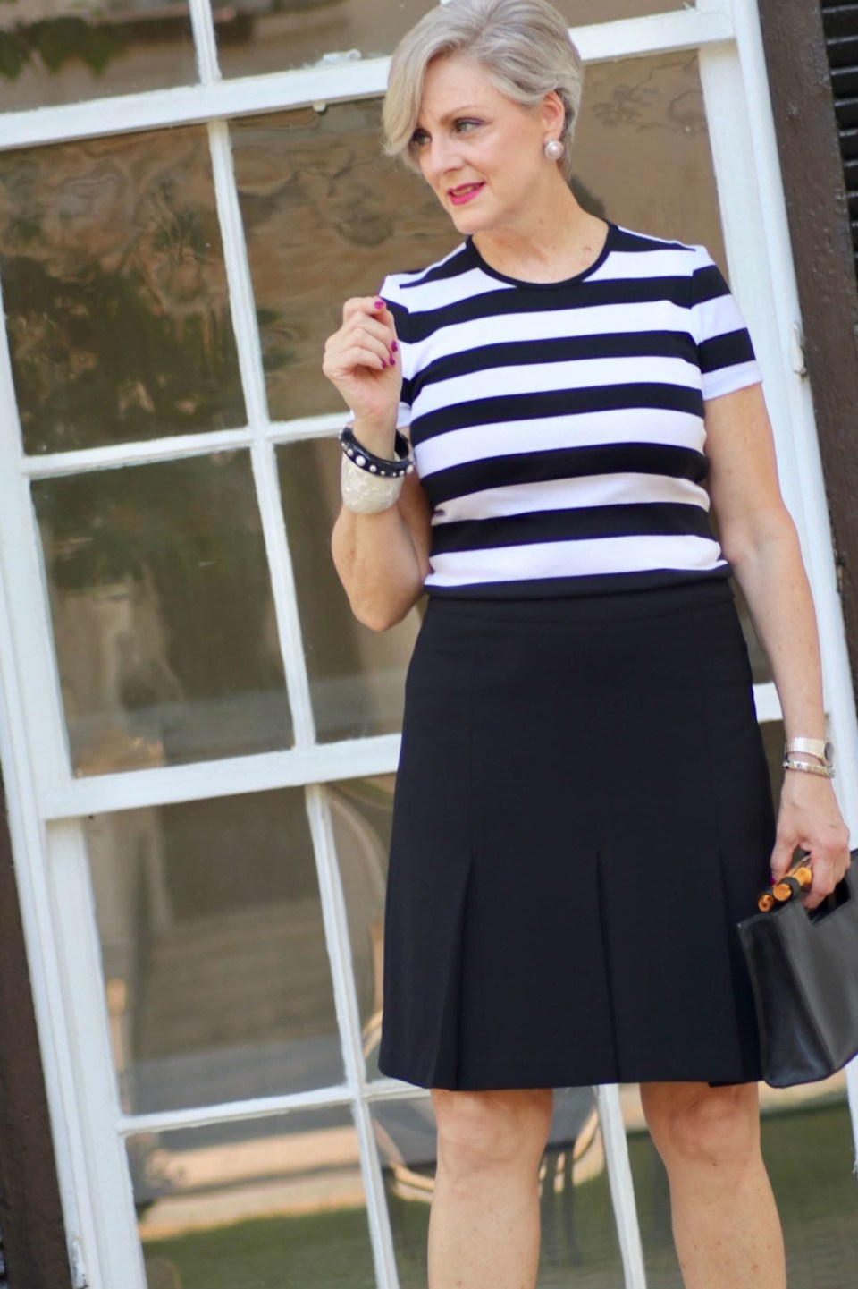 beth from Style at a Certain Age wears a black and white tee, black a-line skirt, pointy toed flats and black handbag