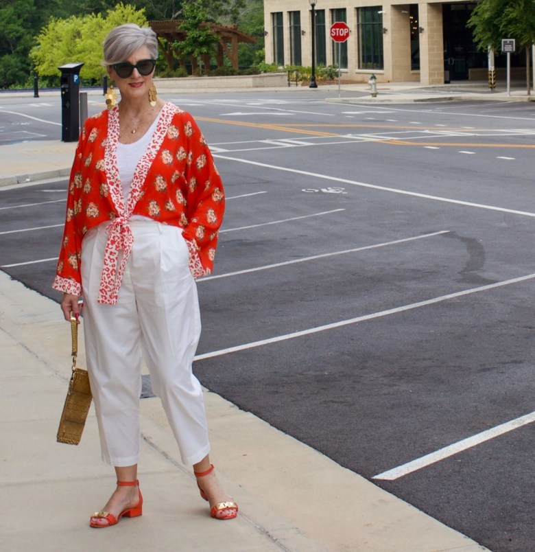 beth from Style at a Certain Age wears a kimono, white cropped chinos, white tee and orange sandals