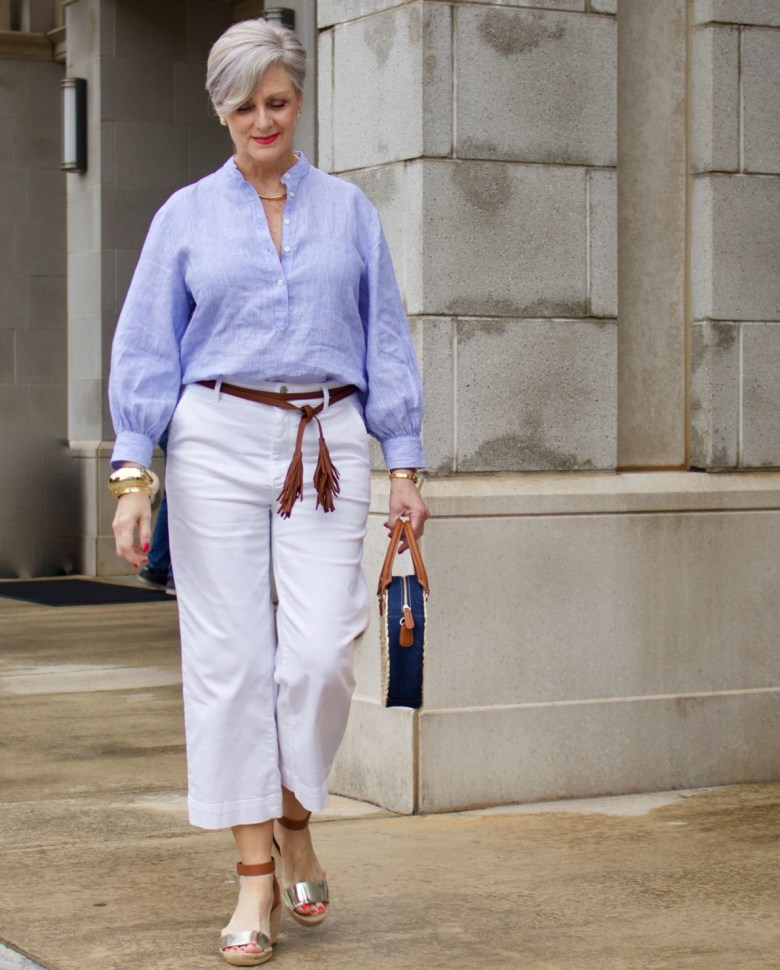 cropped white denim, striped linen shirt, cornhusk handbag, and wedge sandals