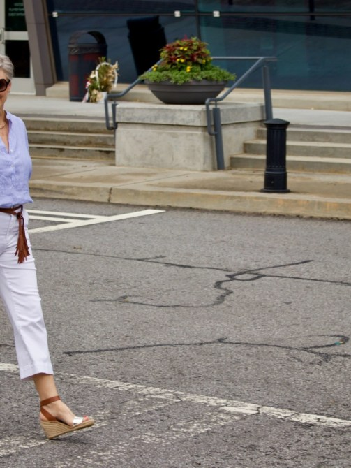 cropped white denim, striped linen shirt, cornhusk handbag, and wedge sandals