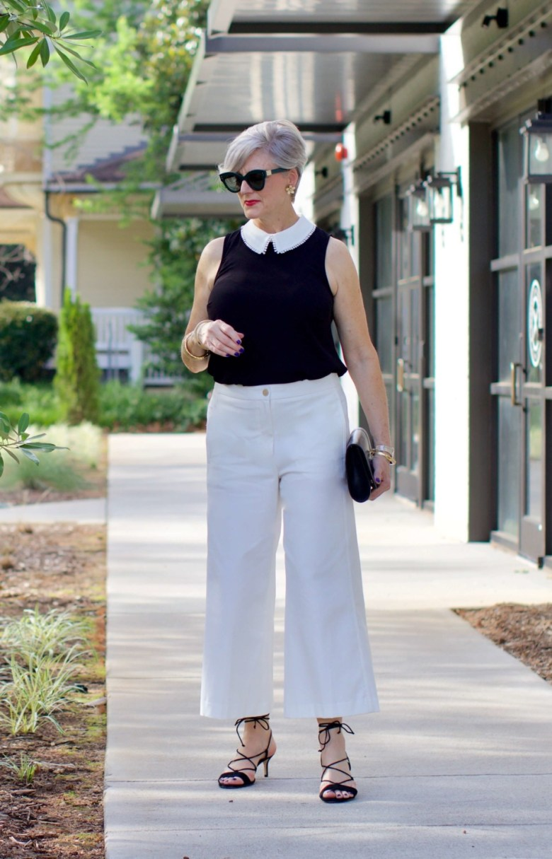 what to wear to work wide leg pants, black blouse, and suede sandals