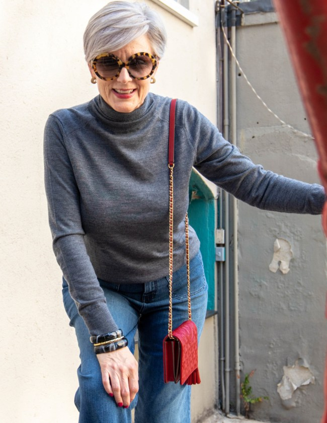 gray turtleneck, red handbag