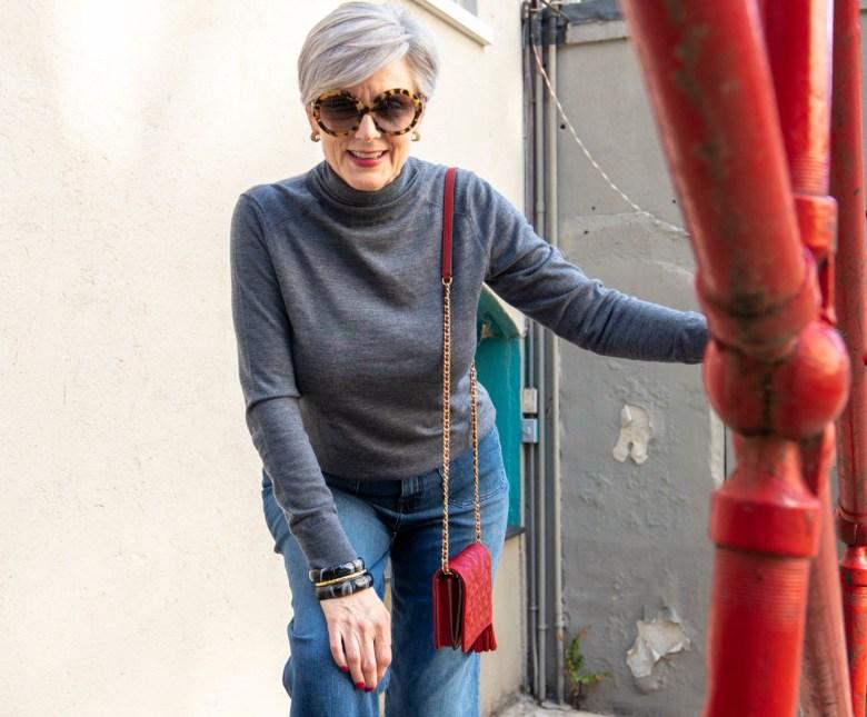 gray turtleneck, red handbag