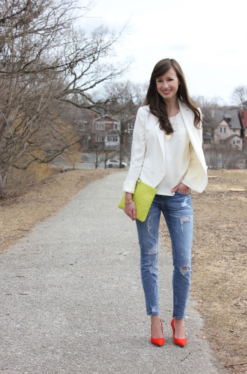 Girl in white blazer, jeans and red heels with a green bag.