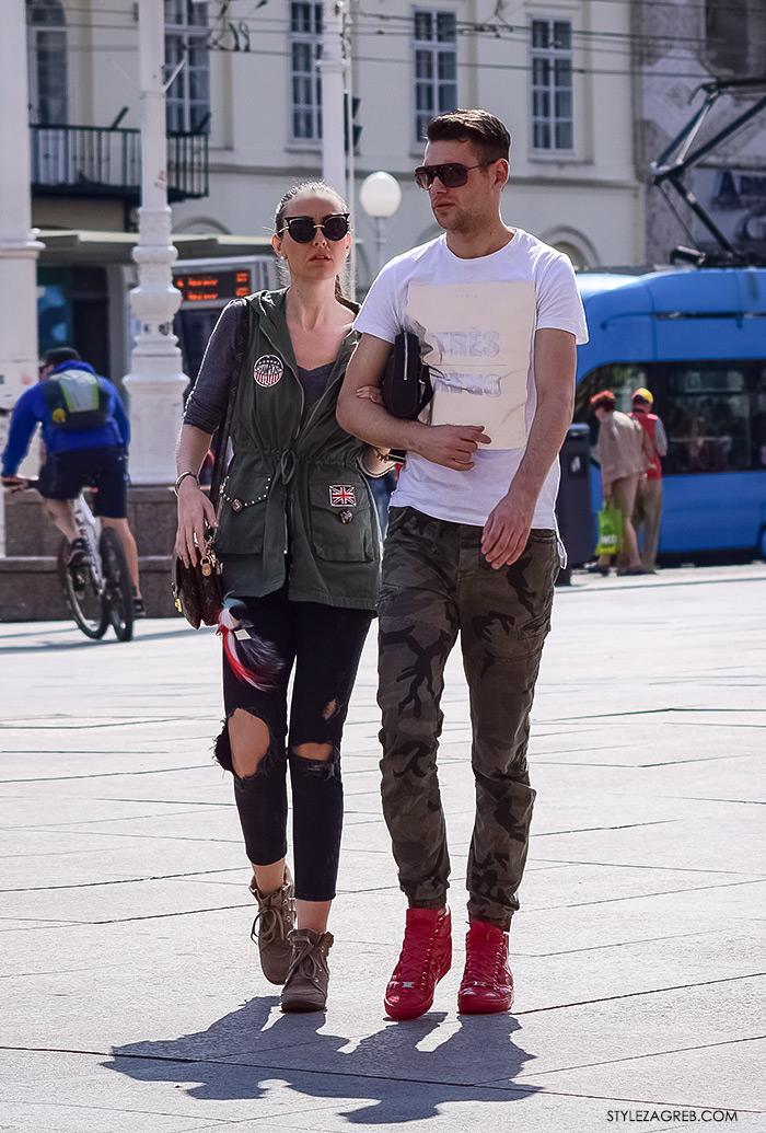 proljetna ulična moda Zagreb street style, zgodan par na ulici, hlače od maskirnog uzroak i crvene muške tenisice